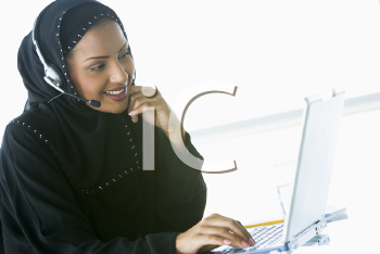 Royalty Free Photo of an Eastern Woman Wearing a Headset at a Laptop