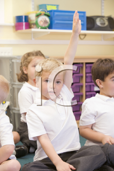 Royalty Free Photo of a Student in Class With His Hand Raised