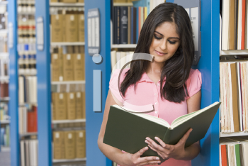 Royalty Free Photo of a Woman Reading in a Library