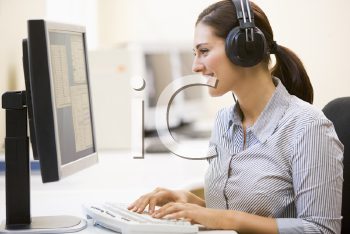 Royalty Free Photo of a Woman at a Computer Wearing a Headset