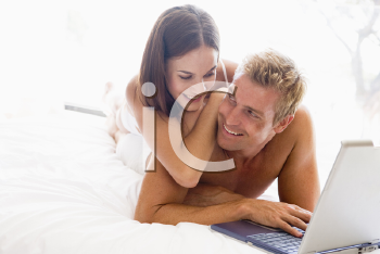 Royalty Free Photo of a Couple in Bed With a Laptop