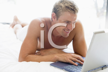 Royalty Free Photo of a Man in Bed With a Laptop