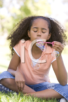 Royalty Free Photo of a Young Girl Blowing Bubbles
