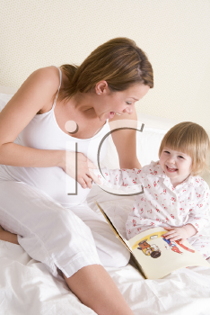 Royalty Free Photo of a Pregnant Woman Reading to Her Daughter