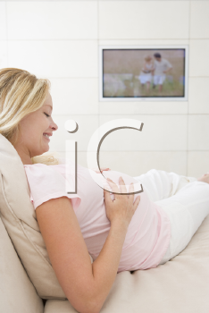 Royalty Free Photo of a Pregnant Woman Watching Television