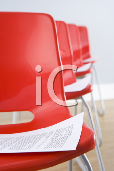 Royalty Free Photo of a Row of Chairs With Papers