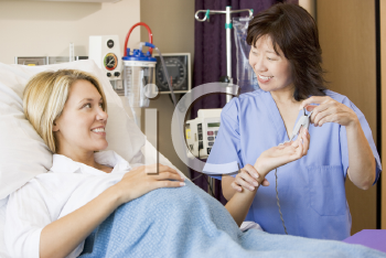 Royalty Free Photo of a Nurse Taking a Pregnant Woman's Temperature