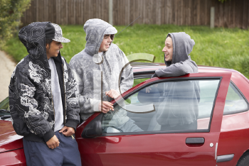 Royalty Free Photo of a Group of Boys With a Car