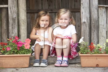 Royalty Free Photo of Two Girls in the Doorway of a Wooden House
