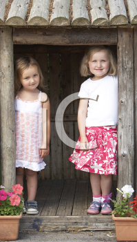 Royalty Free Photo of Girls Playing in a Wooden House