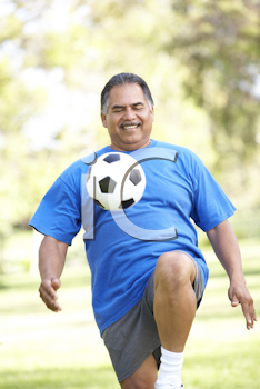 Royalty Free Photo of a Man Bouncing a Soccer Ball on His Knee