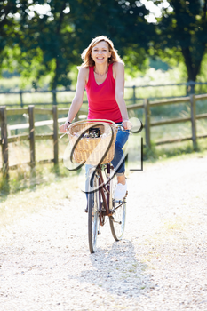 Attractive Woman Riding Bike Along Country Lane