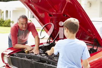 Grandfather And Grandson Working On Restored Classic Car