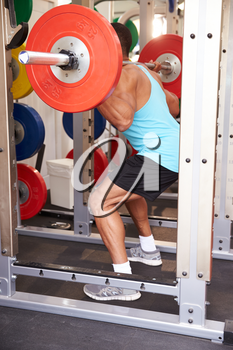 Man weightlifting�barbells at a squat rack in a gym