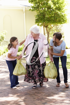 Grandchildren Helping Grandmother To Carry Shopping