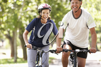 Mature Couple Cycling Through Park