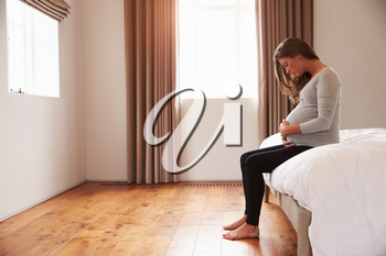 Pregnant Woman Sitting On Bed Holding Belly