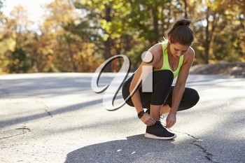 Woman ties her sports shoe before a run, looking down