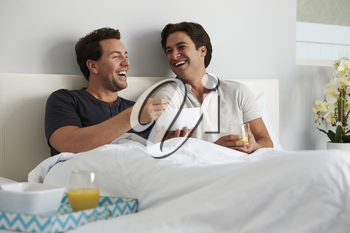 Male gay couple relax in bed eating breakfast together