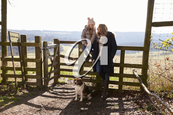 Mum and daughter by rural gate with dog look at each other