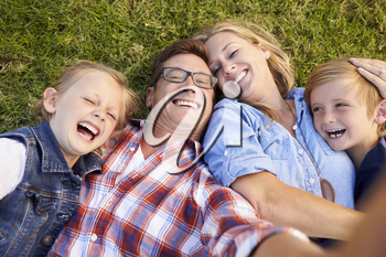 White family lies on grass taking selfie, camera out of shot