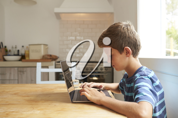 Boy At Home Using Laptop On Kitchen Table