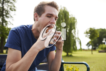Young Man Sitting On Park Bench Eating Burger