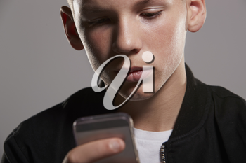 White teenage boy using mobile phone, close up, horizontal
