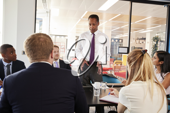 Black male manager stands talking at a business meeting