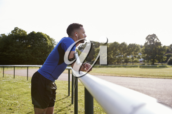 Male athlete at track leaning on fence, three quarter length