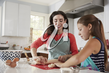 Jewish mother and daughter rolling dough for challah bread