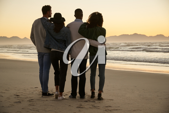 Group Of Friends On Winter Beach Watching Sunrise Together