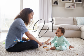 Mixed race mum and toddler son playing in sitting room