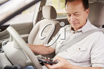 Senior man in car using his smartphone while driving