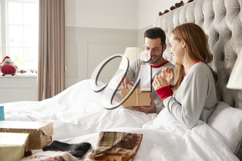 Excited Couple In Bed At Home Opening Gifts On Christmas Day