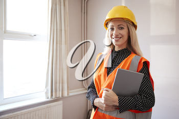 Portrait Of Female Surveyor In Hard Hat And High Visibility Jacket With Digital Tablet Carrying Out House Inspection