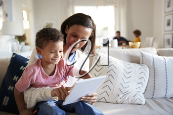 Close up of young mother sitting on a sofa in the living room with her toddler on her knee, reading him a book, father and daughter sitting at a table in the background, focus on foreground