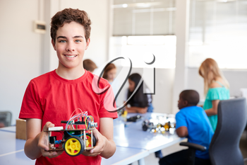 Portrait Of Male Student Building Robot Vehicle In After School Computer Coding Class