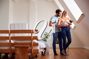 Loving Parents Holding Newborn Baby At Home In Loft Apartment