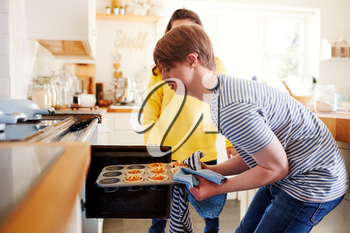 Young Downs Syndrome Couple Taking Homemade Cupcakes Out Of Oven In Kitchen At Home