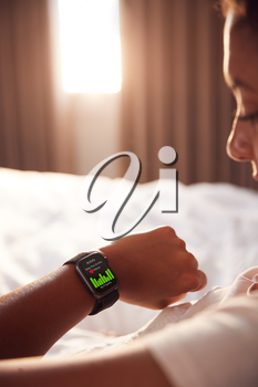 Woman Sitting Up In Bed Looking At Screen Of Smart Watch