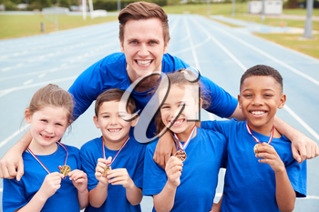 Portrait Of Children With Male Coach Showing Off Winners Medals On Sports Day