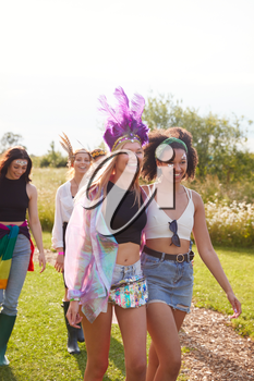 Female Friends Walking Back To Tent After Outdoor Music Festival