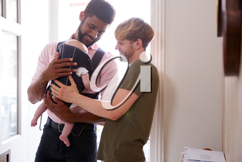 Same Sex Male Couple With Baby Daughter In Sling Opening Front Door Of Home
