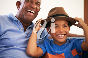 African American Grandfather And Grandson Family Sitting On Sofa With Boy Wearing Hat