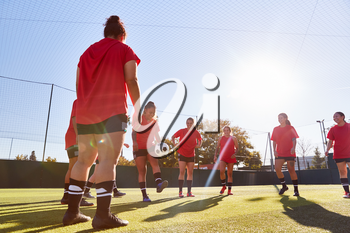 Womens Football Team Kicking Ball Whilst Training For Soccer Match On Outdoor Astro Turf Pitch