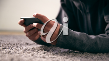Close Up Of Woman At Home Looking At Social Media And Text Messages On Mobile Phone Lying On Carpet
