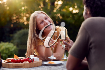 Mature Couple Celebrating With Champagne As They Sit At Table In Garden With Snacks