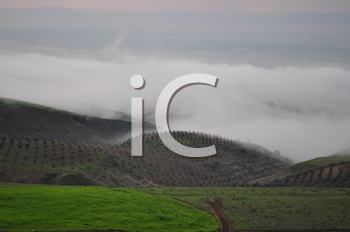 Royalty Free Photo of Grassy Hills, Fog and Mountains