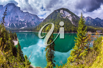 Water reflects mountains and forest. The concept of environmental and hiking. Walk around the lake Lago di Braies, South Tyrol, Italy